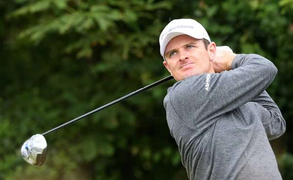 Justin Rose of England plays a shot off