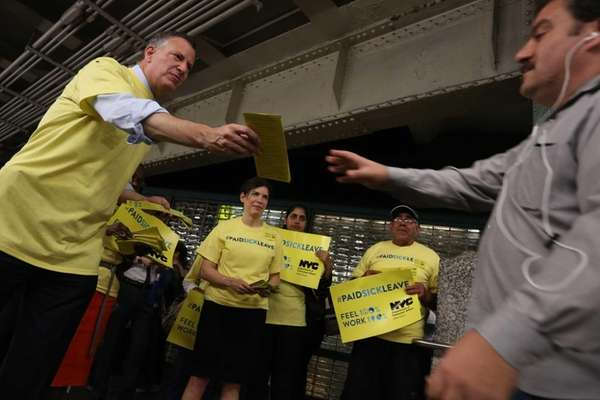 Mayor Bill de Blasio greets commuters and hands
