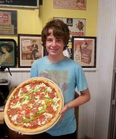 "Thirteen-year-old Andy Mosolino makes ""take-and-bake"" pizzas at The"