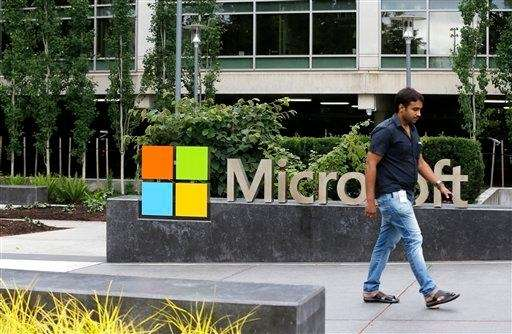 A worker walks past a Microsoft logo outside