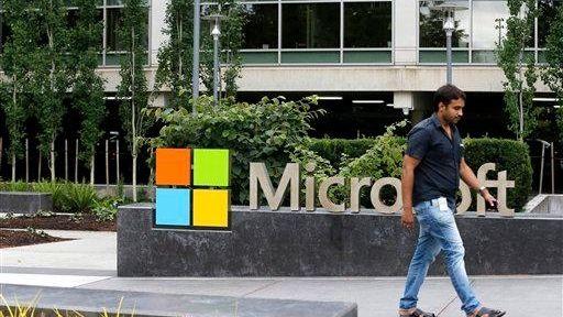 A worker walks past a Microsoft logo outside