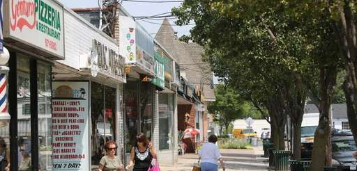 Shoppers walk between businesses along Glen Cove Avenue