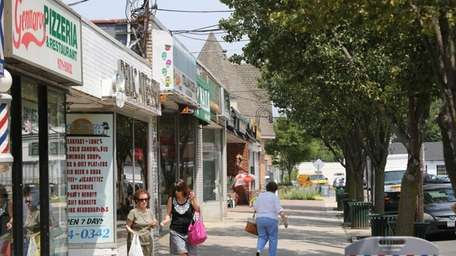Shoppers walk between businesses along Glen Cove Avenue