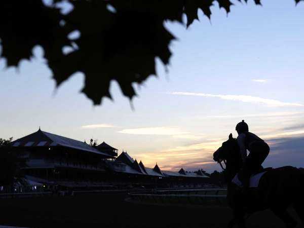 An exercise rider rides a horse during morning