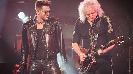 Singer Adam Lambert, left, performs with guitarist Brian