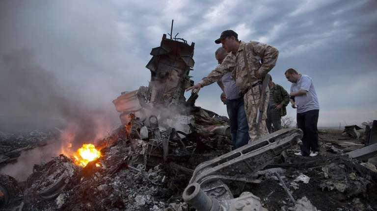 People inspect the crash site of a passenger