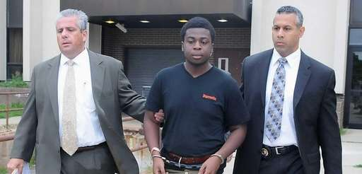 Charles Okonkwo, 18, of Dix Hills, is led
