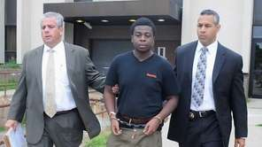 Charles Okonkwo, 18, of Dix Hills, is led