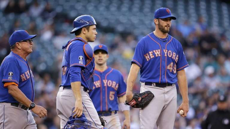 Mets starting pitcher Jonathon Niese, right, waits for