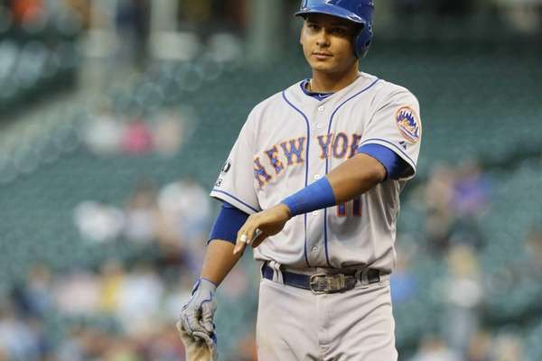The Mets' Ruben Tejada holds his arm up