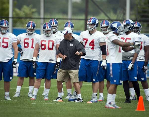 Giants offensive line coach Pat Flaherty demonstrates how