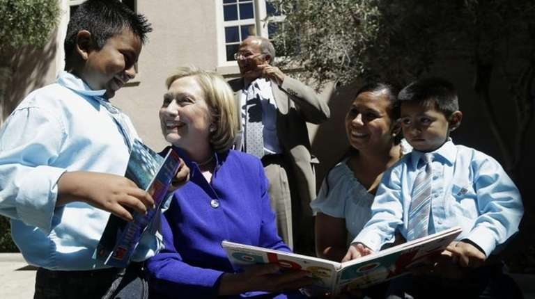 Hillary Clinton, second from left, smiles as she