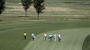A group of golfers makes their way down