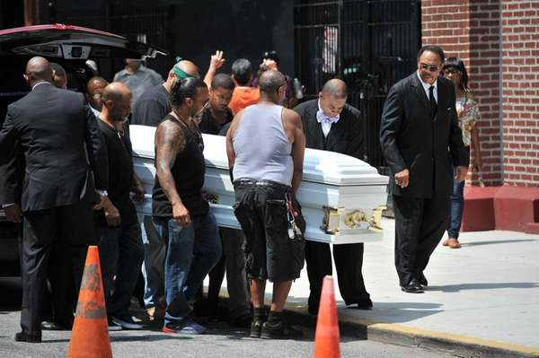 Family and friends move the casket of Eric
