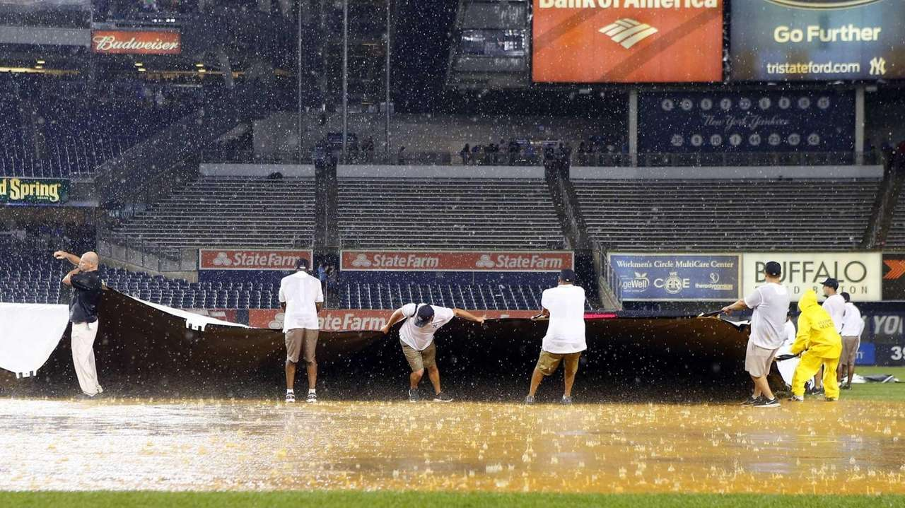 Members of the grounds crew struggle with the