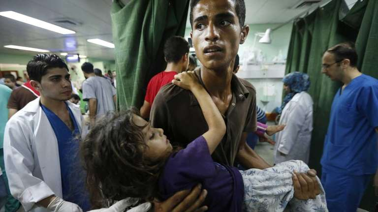 A Palestinian youth carries a child, wounded in
