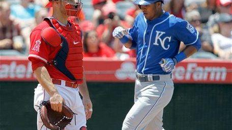 The Kansas City Royals' Jimmy Paredes scores behind