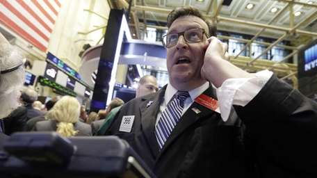 Trader Benedict Willis uses his cellphone as he