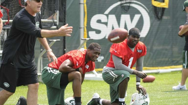 Quarterback coach David Lee ,left, works with his