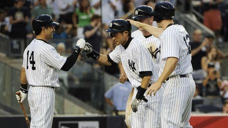Yankees' Ichiro Suzuki is congratulated on his three-run