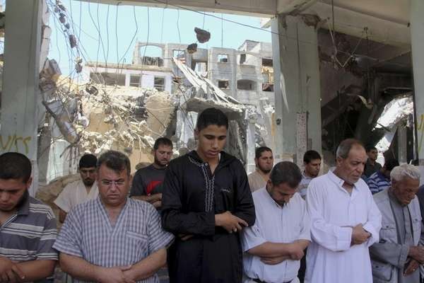 Palestinians pray the Friday prayer inside a destroyed