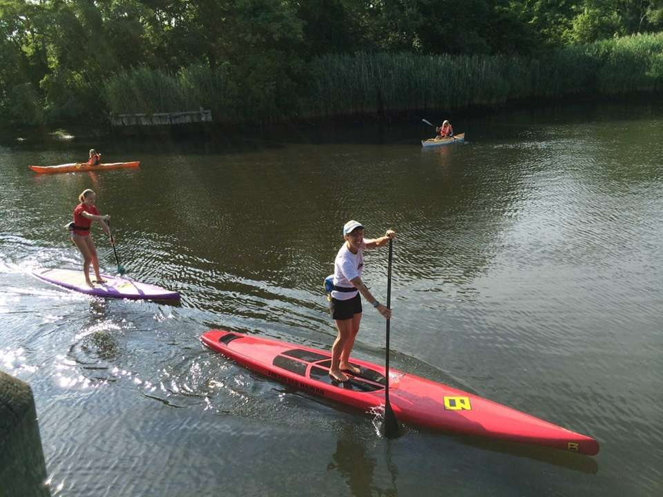 Stand-up paddle boarders, kayakers, and canoers from Long