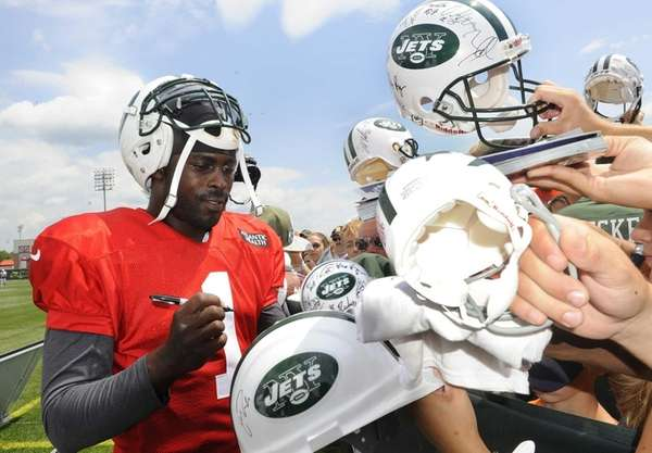 Jets quarterback Michael Vick signs autographs after training