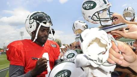 Jets quarterback Michael Vick signs autographs after training