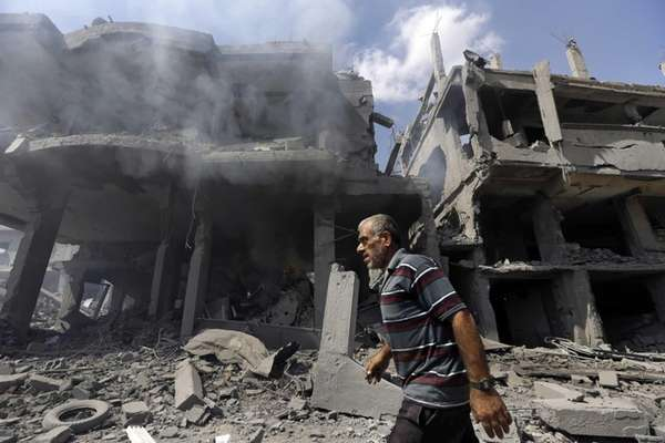 A Palestinian man walks by buildings heavily damaged