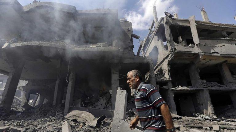 A Palestinian man walks by buildings heavily damaged