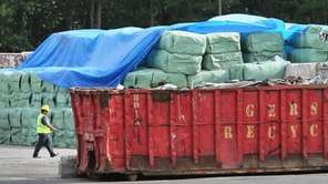 A worker walks past bales of garbage stacked