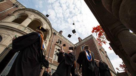 Graduates of Webb Institute throwing their caps in