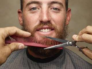 Tennis pro Christian Guevara gets his beard trimmed