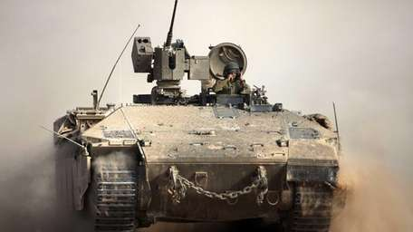 An Israeli armored personnel carrier rolls along the