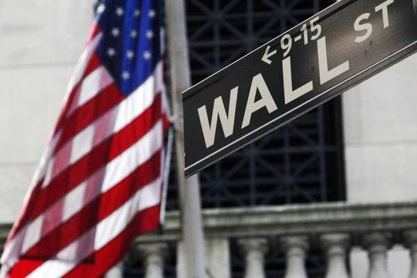 An American flag and Wall Street sign outside