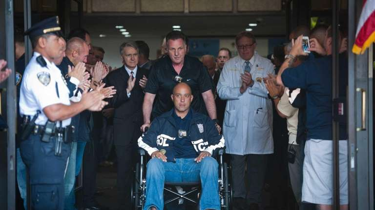 NYPD Det. Joseph Trovato pushes the wheelchair of