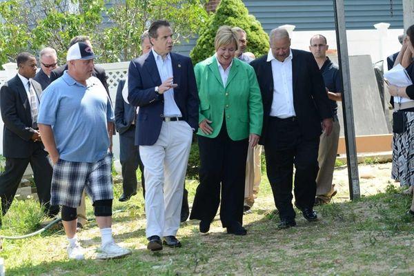 Homeowner of Dan Ehrick, left, walks on July
