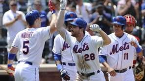The Mets' Daniel Murphy gestures after scoring on