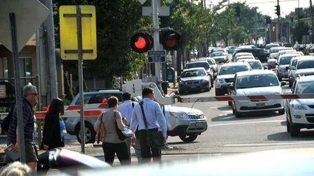 Commuters wait to cross Hillside Avenue after disembarking