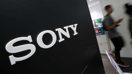 Visitors walk past a logo of Sony at