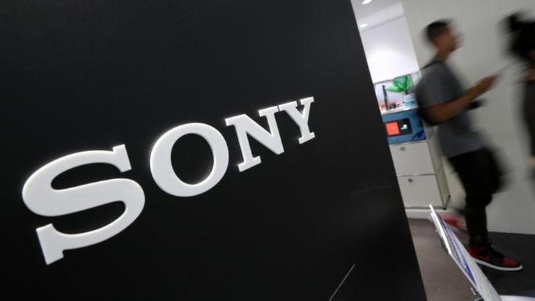 Visitors walk past a logo of Sony at