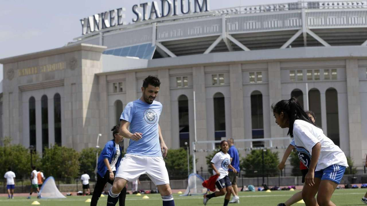 David Villa, left, plays soccer with kids from