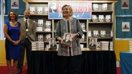 Hillary Clinton holds her new book,
