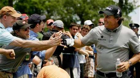 Phil Mickelson is greeted by fans as he
