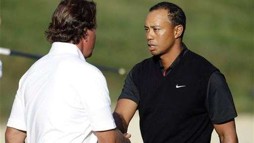 Tiger Woods and Phil Mickelson shake hands after