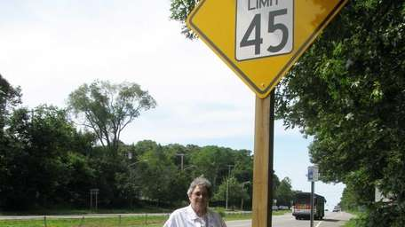Florence Singler stands next to a sign warning