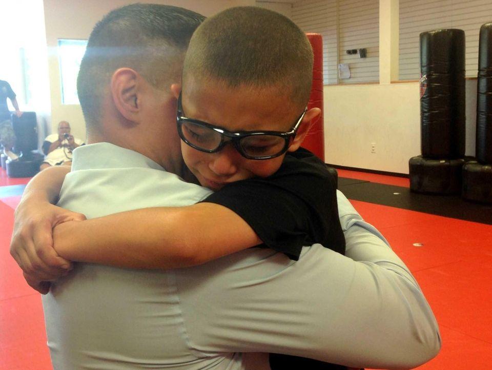 Mikey Ortiz, 9, wraps his arms around his