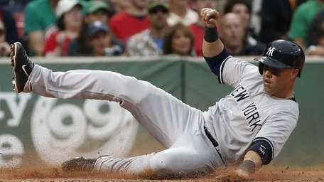 The Yankees' Carlos Beltran slides safely into home