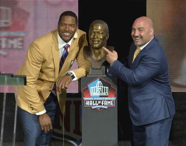 Inductee Michael Strahan, left, poses next to his