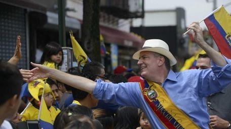 Mayor Bill de Blasio greets spectators as he